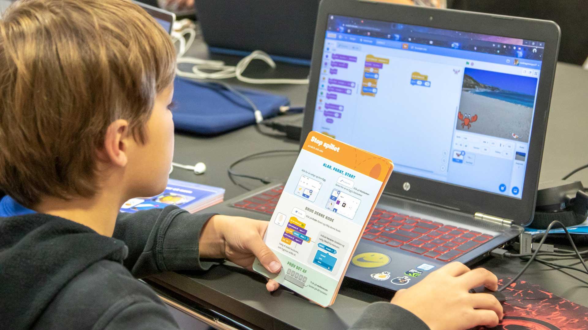 Barn arbejder med Scratch kode-kort ved computer.